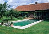 Swimming-Pool an Terrasse mit Sitzgruppe aus Holz, Wintergarten mit Kletterpflanzen, Apfelbaum (Malus) im Rasen