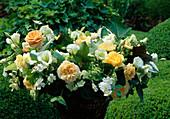 Üppiger Strauss aus Rosa (Rosen), Eustoma (Praeirieenzian), Hydrangea (Hortensie), Mentha (Ananasminze), Blättern von Hosta (Funkie), Hedera (Efeu) und Heuchera (Purpurglöckchen) in Korbvase