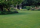 Blick über Rasenfläche auf offenen Pavillon und Staudenbeet