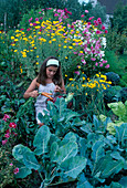 Mädchen mit frisch geerntetem Gemüse im Korb, dahinter hohe Blühpflanzen