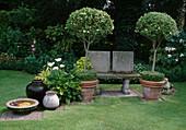 Gartenbank aus Stein, Ligustrum (Liguster) Stämme unterpflanzt mit Buxus (Buchs), Zantedeschia aethiopica (Kalla), Vasen und Vogeltränke