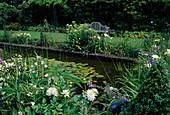 Architektonischer Gartenteich mit Nymphaea (Seerosen), Stauden und Sommerblumen als Uferbepflanzung, Holzbank am Beetrand