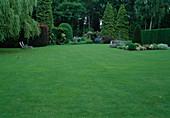 Rasenfläche mit Blick auf Beete, Hecken und Bäume, Holzliegen unter Trauerweide