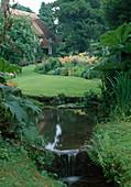 Bachlauf im Landhaus-Garten, Blick über Rasenfläche zum Staudenbeet