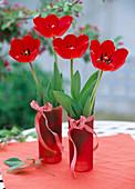 Rote Tulpen in roten Gläsern