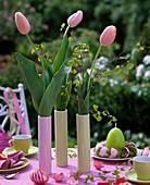 Schlanke Vasen mit Tulpen und Birkenzweigen als Tischdeko