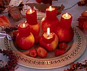 Malus (Apfel), ausgehöhlt mit roten Stumpenkerzen,