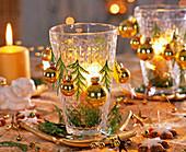Gläser als Windlichter dekoriert mit goldenen Kugeln
