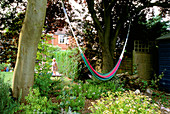 A HAMMOCK STRUNG BETWEEN TWO TREES IN Rosemary PEARSONS Garden, READING