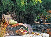 Liegestuhl vor Phyllostachys (Bambus) am Teich