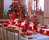 Tischdekoration mit Picea glauca 'Conica' in roten Töpfen und roten