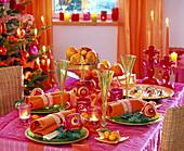Orientalische Weihnachtstischdeko: Orange Servietten zusammengerollt