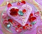 Torte mit Blüte von Rosa (Rose, rot), Blütenblätter auf Glasteller