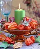 Grüne Kerze mit Physalis (Lampions) und Hydrangea (Hortensien) Glasschale