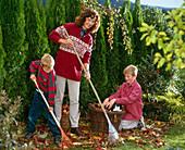 Frau mit zwei Jungen beim Laubrechen