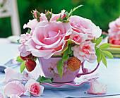 Blüten von Rosa (Rosen), Fragaria (Erdbeeren) in Kaffeetasse, Blütenblätter