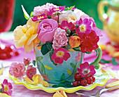 Blüten von Rosa (Rosen, gelb, rosa und rot) in bunter Kaffeetasse