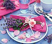 Sträußchen aus Lavandula (Lavendel) und Rosa (Rose) auf pinker Serviette