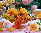 Rosa (Rosen, orange), Alchemilla (Frauenmantel) in oranger Glasschale