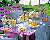 Tischdeko mit gelben Lilium (Lilien), hellblau gedeckter Kaffeetisch