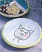 Keramikteller mit aufgemaltem Katzengesicht,