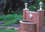 Wasserspeier 'Engelkopf' mit gemauertem Becken an gemauerter Klinkerwand