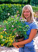 Frau mit Pelargonium 'Sweet Mimose' (Duftgeranie)