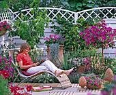 Terrassenbeet mit mediterranem Ambiente, Korbliege mit Frau