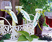 Bottles with sambucus berries juice on metal tray