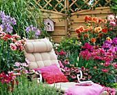 Liegestuhl im Blumenbeet vor Sichtschutzwand