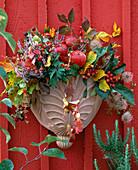 Herbstliches Gesteck mit Beeren, Früchten und Herbstlaub