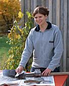 Pflege von Gartengeräten: Frau ölt Schaufel von Spaten ein