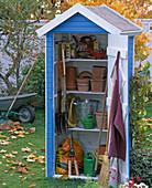 Kleines Gerätehaus mit Töpfen, Dünge- und Pflanzenschutzmitteln, Spaten