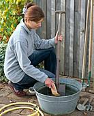 Frau reinigt Spaten mit Bürste und Wasser