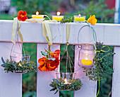 Windlichter mit kleinen Kränzen aus Salvia (Salbei), Thymus (Thymian)