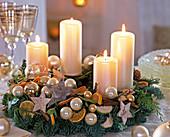 Adventskranz mit weißen Kerzen, Kugeln, Sternen, Orangenscheiben und Zimtstangen