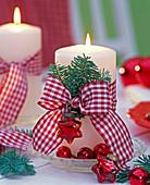 Zweige von Abies (Tanne) mit rot - weiß karierter Schleife an weißer Kerze