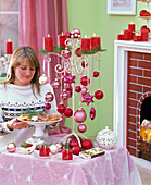 Frau mit Plätzchenschale sitzt am Tisch mit weihnachtlicher Dekoration