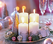 Adventskranz mit weißen Stumpenkerzen auf Silberteller mit Cupressus