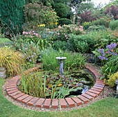 BRICK EDGED POND LITTLE Boy FOUNTAIN, DENDRANTHEMA 'CLARA CURTIS, Iris LAEVIGATA 'SNOW DRIFT'. VALE END, Surrey