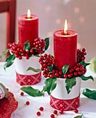 Ilex (Stechpalme) mit roten Kerzen in weißen, mit Band dekorierten Bechern