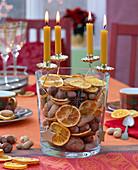 Adventskranz mit gelben Kerzen auf Vase gefüllt mit getrockneten Orangenscheiben