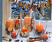 Orange Kerzen in Gläsern gefüllt mit getrockneten Scheiben von Malus (Äpfeln)