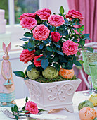 Rosa (Topfrose) in viereckigem Relief-Übertopf, Ostereiern und -hasen
