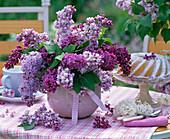 Strauß aus Syringa (Flieder) in lila Vase auf kariertem Tischtuch, Kuchen