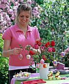 Frau schmückt Osterstrauß aus Tulipa (Tulpen) und Corylus (Haselnuß)