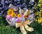 Korb mit Ostereiern, Blüten von Primula (Primeln), Schokoladenhasen