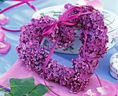Herz aus Syringa (Flieder) mit Schleife an Porzellandose gelehnt, Serviette