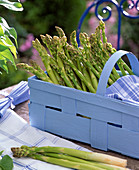 Green asparagus in light blue woodchip basket, kitchen towel