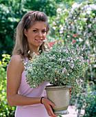 Junge Frau mit Pelargonium fragans 'Variegatum' (Duftgeranie)